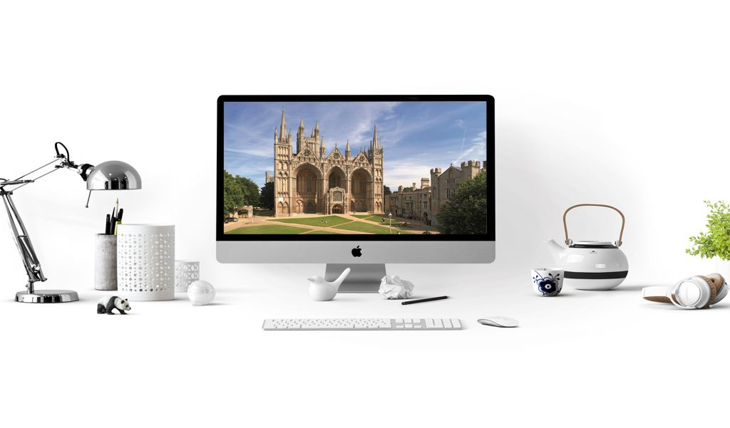 Peterborough Cathedral screen saver on iMac with desktop writing utensils, lamp, and a small kettle with cup all on a white background