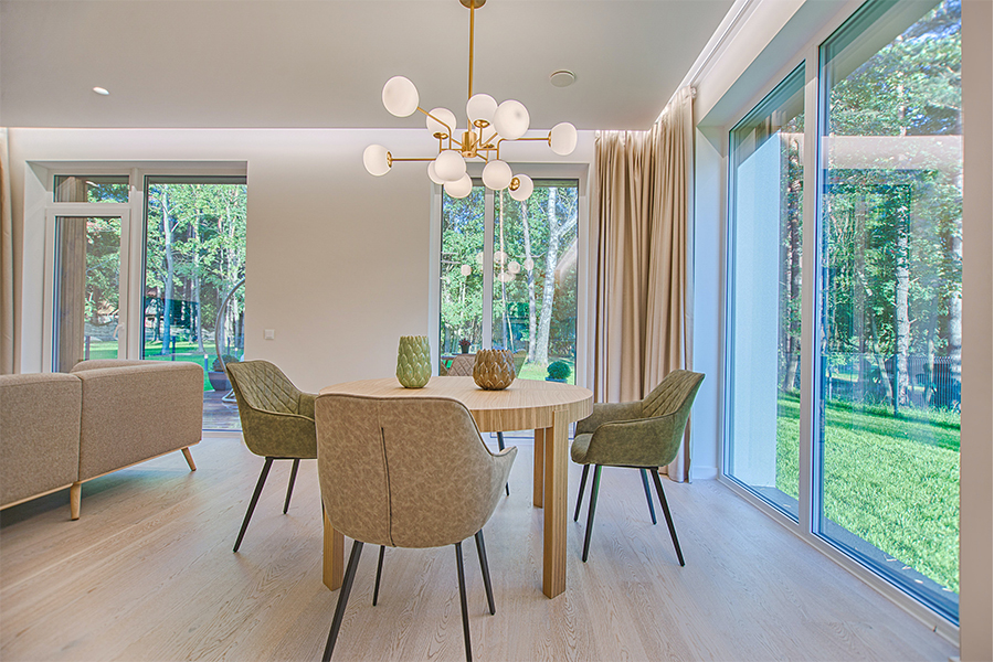 Inside a modern home with three large pristine cleaned glass patio doors, with views looking out outwards towards the tree lined garden.