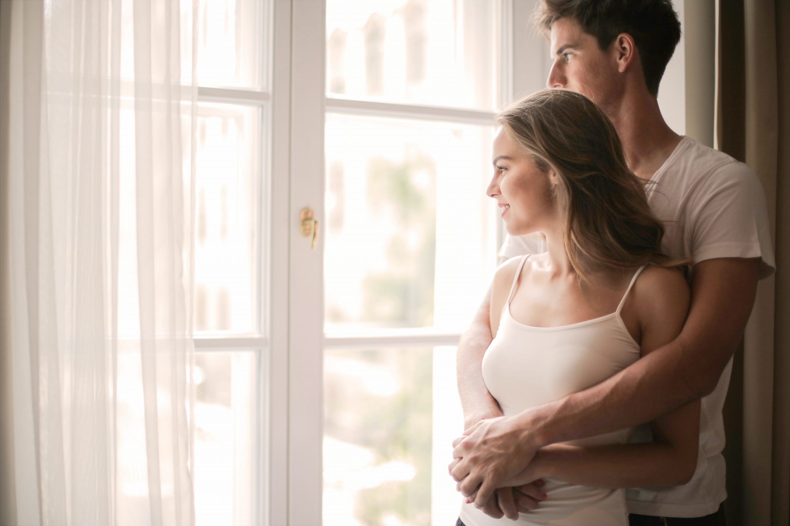 Young man holding young lady in front with arms around her, admiring the view through clean glass French doors